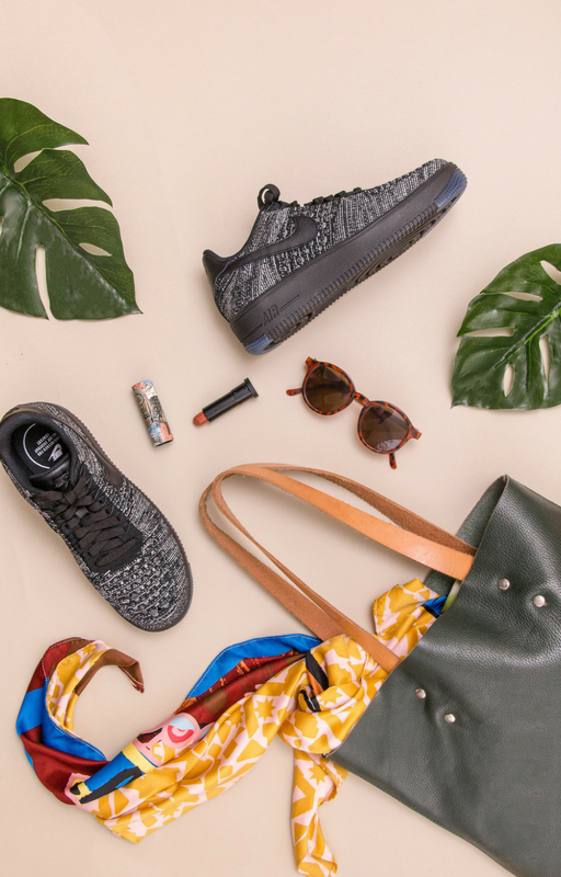 Blog image with one shoe, leaf, sunglasses, and a bag on the nude background