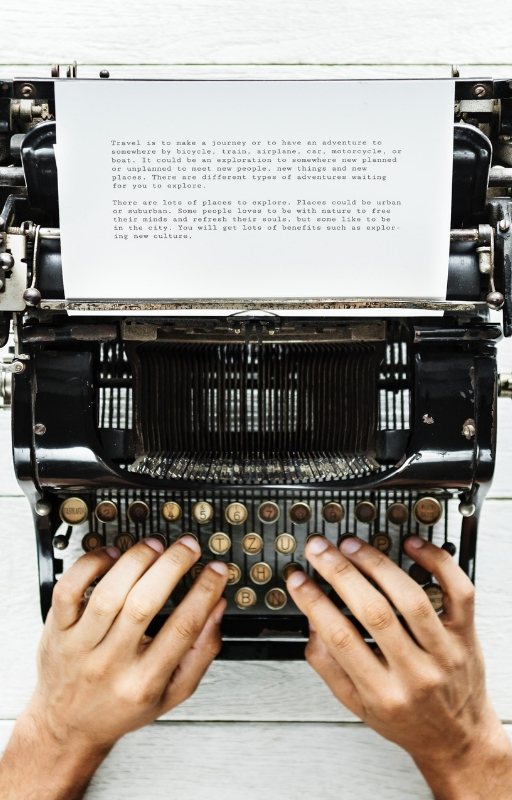 Two hands typing on a typewriter