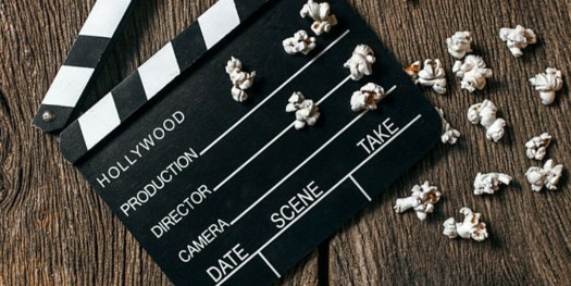 An image of a clapper board placed on a wooden surface with 19 popcorns positioned at the bottom of the clapper board