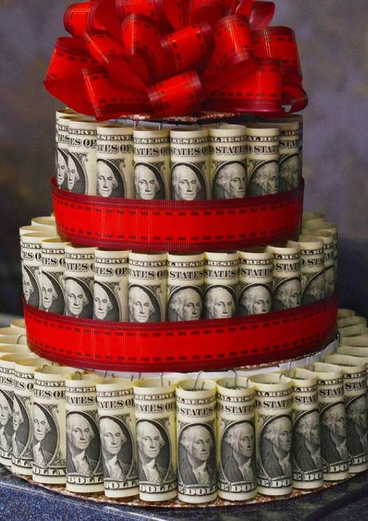 Image of European currency made in shape of a three layered cake with red bow on the top