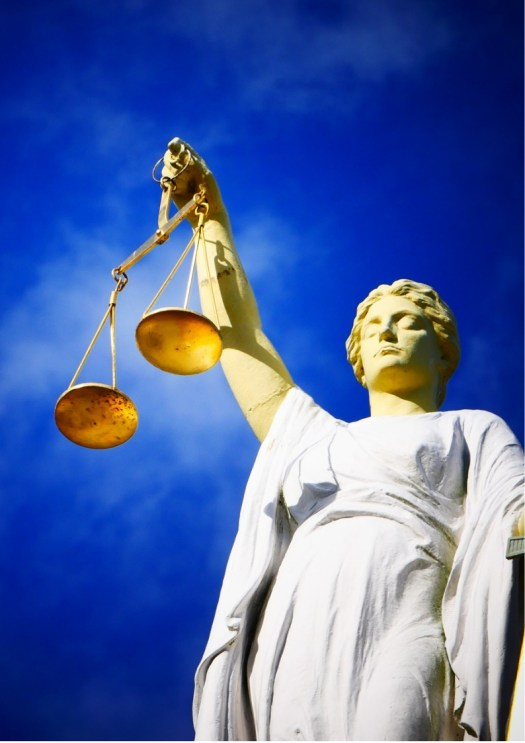 An image of a lady justice with blue sky as the background