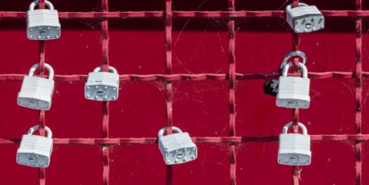 An image of a wire in criss cross position with red background where 8 locks are placed in the wire.