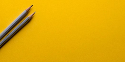 Yellow background with two pencils placed at the left corner