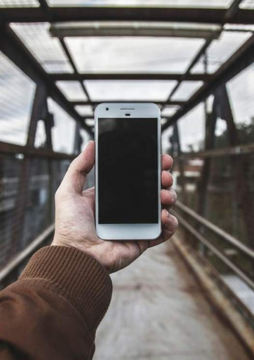 Image of a hand holding a mobile phone with a bridge background