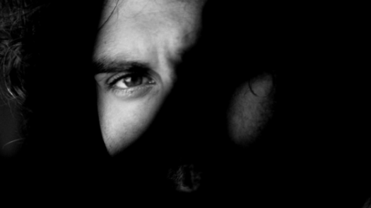 Black and white photo of a man's face with one eye visible and one eye hidden behind shadow