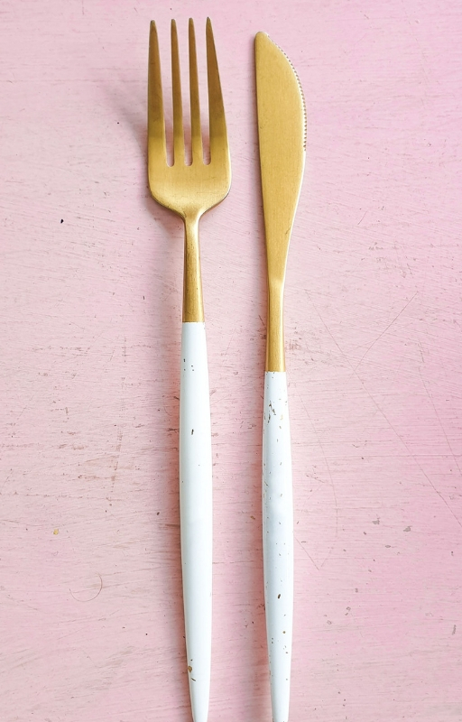 Fork and knife on a pink background