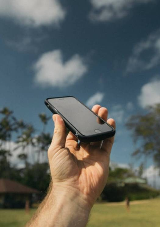 Image of a hand holding a phone in air with clouds as its background