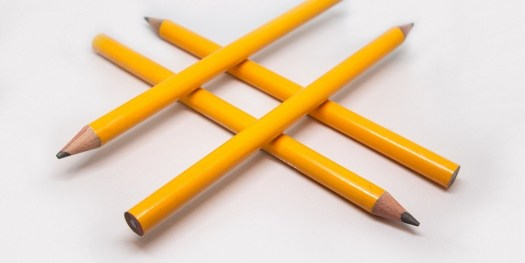 Image of four yellow pencils placed in a hashtag symbol on white background