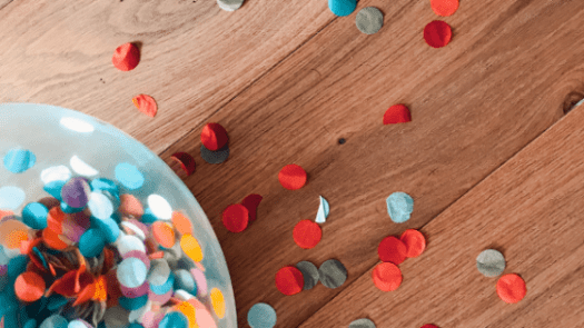 illustration image showing an assorted color of sprinkle paper dots on brown wooden floor