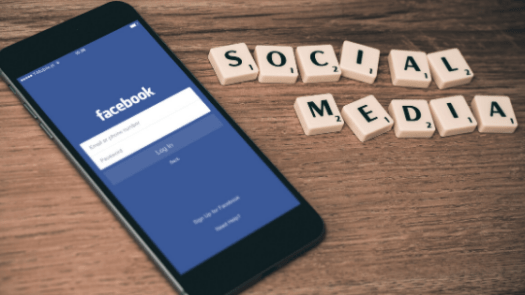 A phone with facebook login page and 'social media' written in blocks