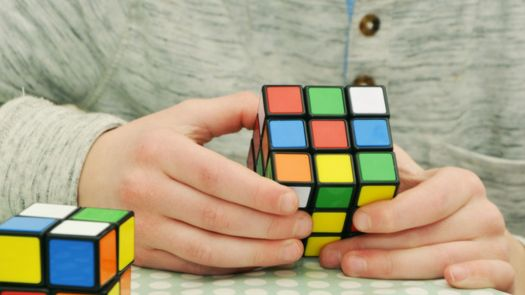 A man is solving the rubik's cube.