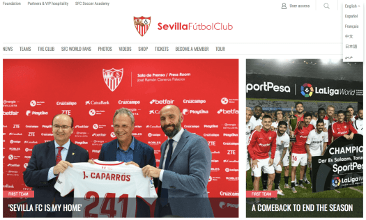Homepage of Sevilla FC website with three people holding the team jersey on left and the football team posing for the camera on right