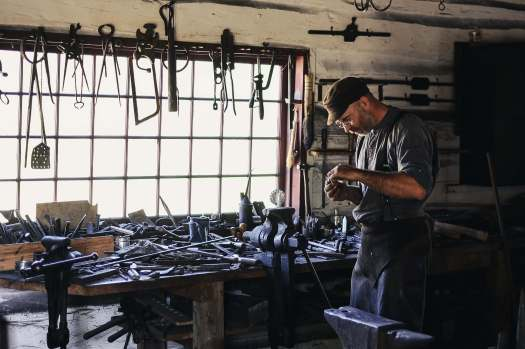 A metalsmith working in a room full of metal objects