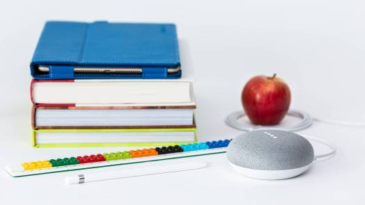 A pile of books, a voice interface device, a pen and an apple kept close to each other