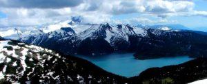 Figura 4.2 Mt. Garibaldi (fondo a la izquierda, mirando desde el norte) con el lago Garibaldi en el primer plano. El pico volcánico en el centro es Mt. Precio y el pico de cima plana oscura es la tabla. Los tres de estos volcanes estaban activos durante la última glaciación. [Foto SE]