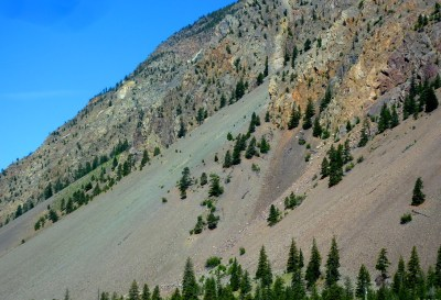 Photograph of an area with very effective frost-wedging near to Keremeos, BC. The fragments that have been wedged away from the cliffs above have accumulated in a talus deposit at the base of the slope. The rocks in this area have quite varied colours, and those are reflected in the colours of the talus.
