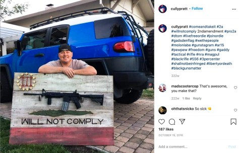 Solano County Sheriff's Sgt. Cully Pratt poses in a driveway with a Three Percenter-themed rifle display rack he made for his colleague, Sgt. Roy Stockton. A black AR-15 semiautomatic rifle is mounted on the rack.