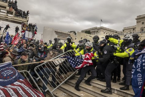 Supporters of President Trump clash with police at the United States Capitol on Jan. 6, 2021. A Three Percenter flag is visible in the lower left foreground of the frame.
