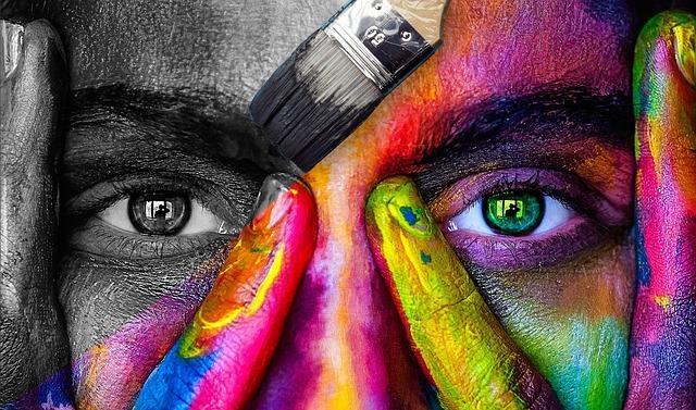 Photo du haut d'un visage, à moitié en noir et blanc, à moitié couvert de peinture multicolore.