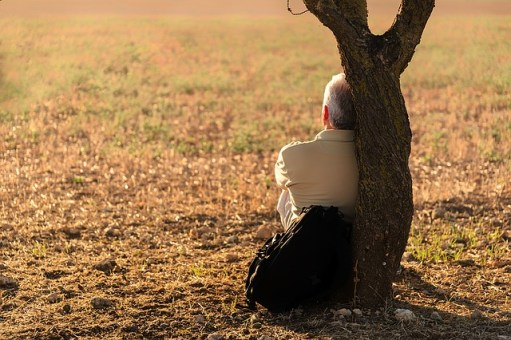 Homme seul contre un arbre.