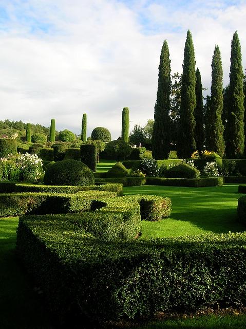 Photo d'un jardin à la française, mêlant à la fois de la pelouse, des haies courbes et géométriques, des buissons de fleurs et des arbres.
