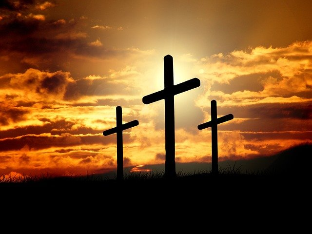 Photo de trois grandes croix de crucifixion sur fond de ciel orangé.