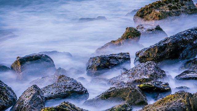 Photo de rocher marins, entourés d'un effet de brume (sans doute des aller/retour de vagues en pose très lente).