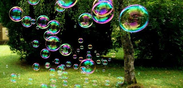 Photo de bulles de savon de différentes tailles, volant en extérieur.