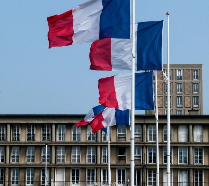 Des drapeaux français devant un bâtiment public.