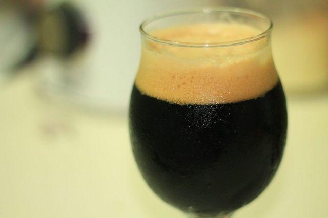 Pohár s tmavým pivom. Stout alebo Porter.