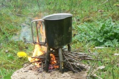 Voor het koken heb je soms niet veel nodig. Een pannetje, in wat voor vorm dan ook, en een vuurtje volstaan. Luxer maken kan ook, zoals hier met 4 stokjes (wat zijn de voordelen?)