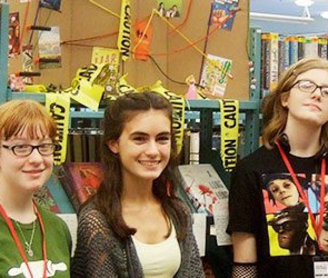 Group Of Teen Volunteers In Front Of Book Display