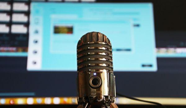 Micrófono para podcast, en frente de un ordenador de mesa.