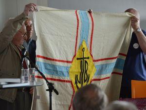 Gaston Derkinderen, oudste lid van Op Stoapel, neemt de vlag in ontvangst van Ward Foubert, Dirigent van de voormalige Boelwerf harmonie