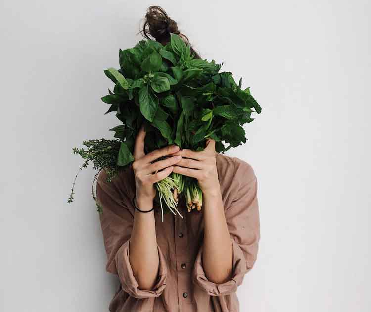 Vegetarian diet, a woman holding green vegetables in front of her face