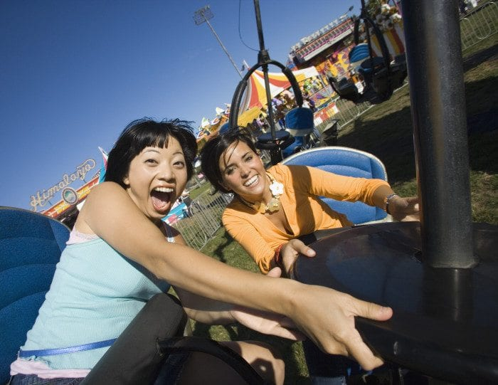 two girls taking selfies on a roller coaster.
