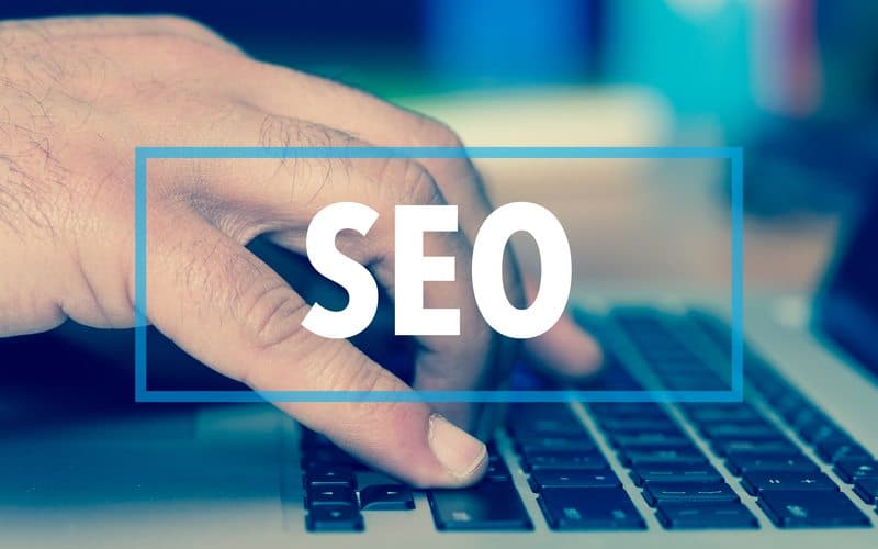 """person typing on laptop with """"SEO"""" imposed front and center of image"""