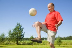 Older male hitting soccer ball with his knee.