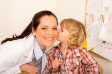 Child giving appreciative kiss to his health care worker.