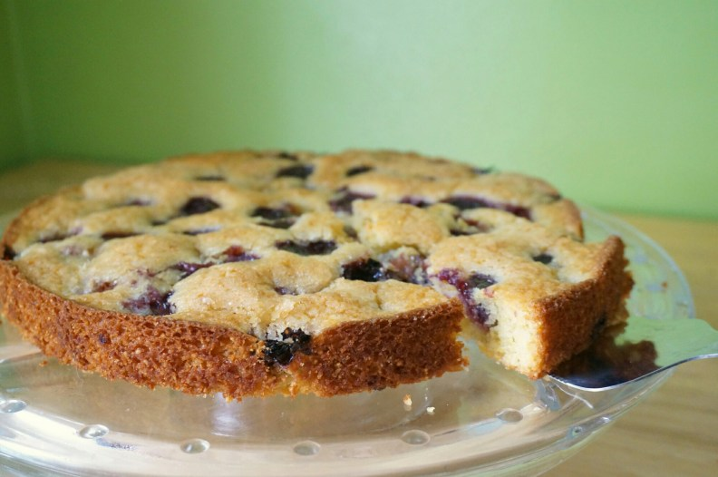 A whole light and airy cherry cake sits on a glass cake plate; a cake server has slightly pulled out one slice.