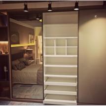 Armário com prateleiras, nichos, gavetas e porta de correr com espelho