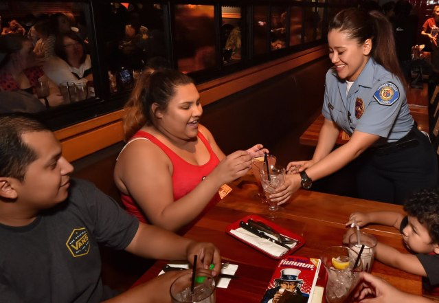 CLARISSA Felix of Lake Elsinore gets her lemonade from Garden Grove PD Cadet Michele Estrada as police raise money for Special Olympics during the Tip a Cop charity event at a Red Robin restaurant. Photo by Steven Georges/Behind the Badge OC