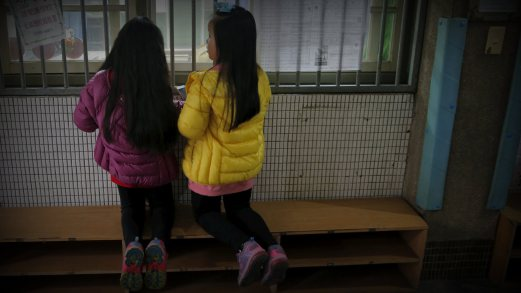 Children Watch As Voters Cast Their Ballots At A Polling Station During General Elections In Taipei