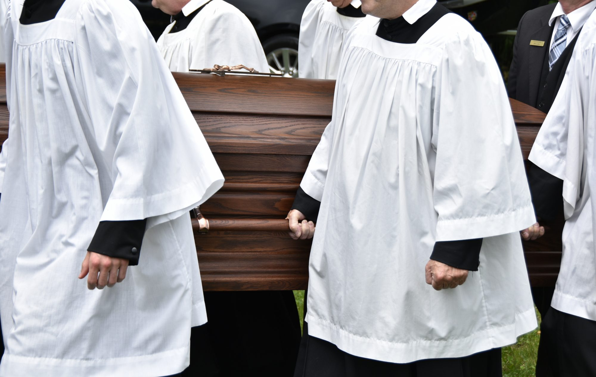 The Oratorian Fathers carry the casket at the burial