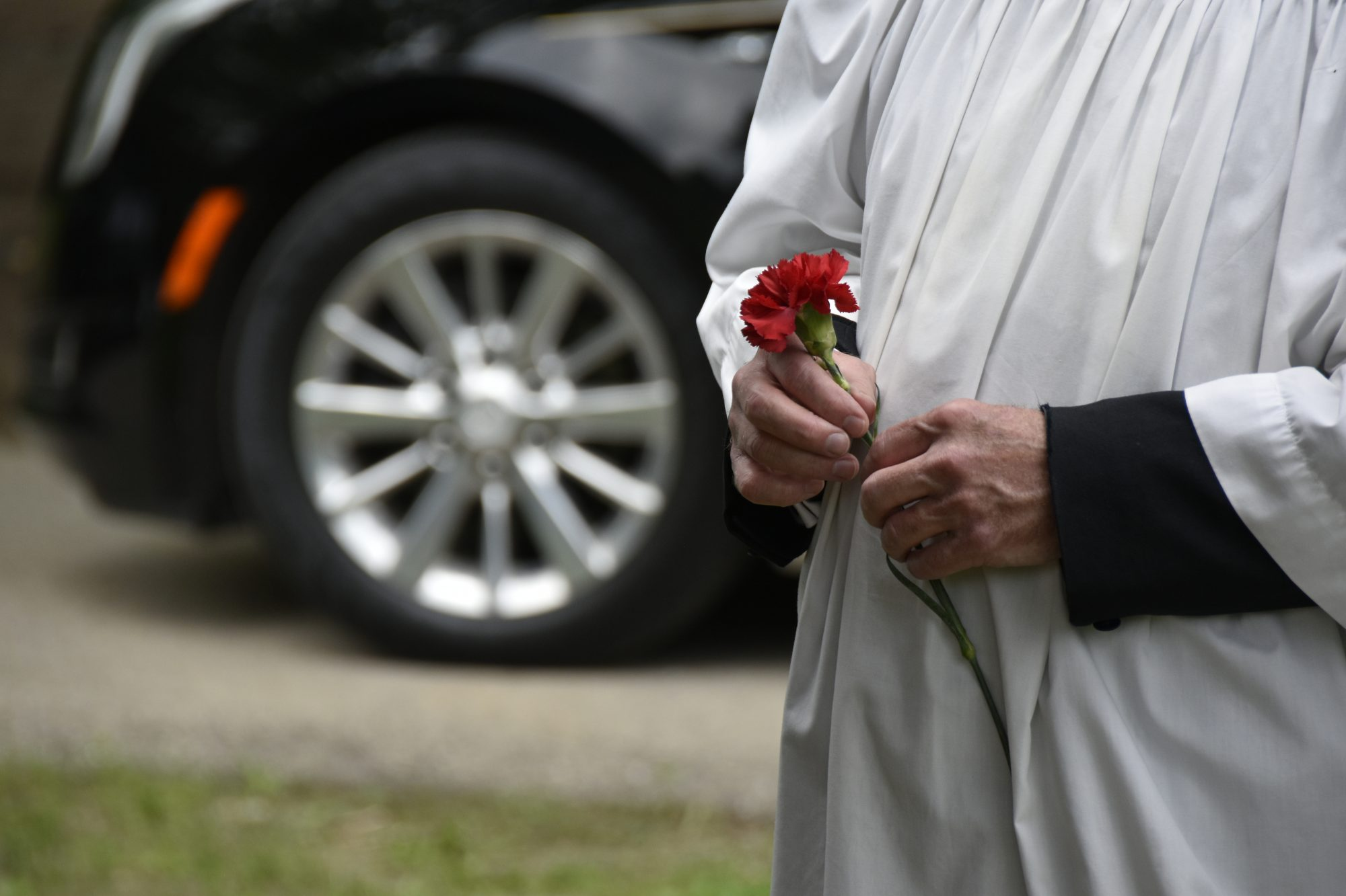 An Oratorian holds a flower at the burial