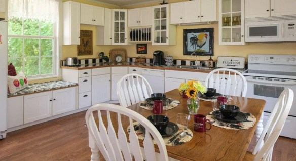 Cheery white and yellow farmhouse kitchen with table set for dining.