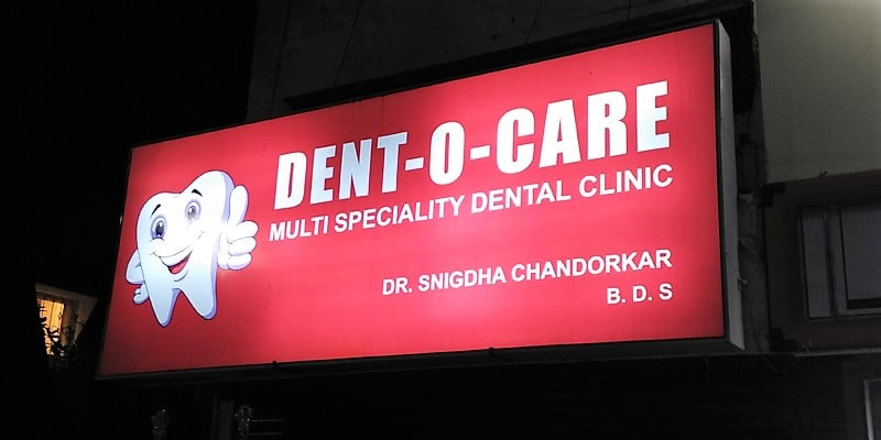 flex printed backlit glow sign board with lights glowing within for the dent-o-care clinic