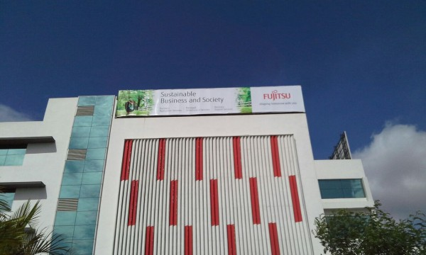 flex hoarding installed on the top of a very tall building at the Fujitsu Company