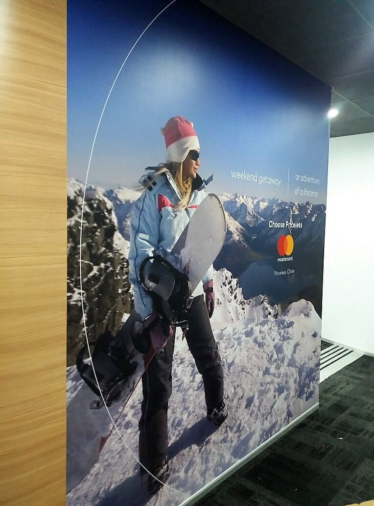 Large-sized custom wallpaper print of a woman holding a ski board installed in an office