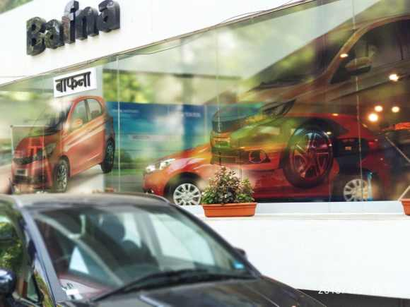 transparent window vinyl pasted on the glass front of a car outlet shows an image of a red car and also allows you to look inside the showroom